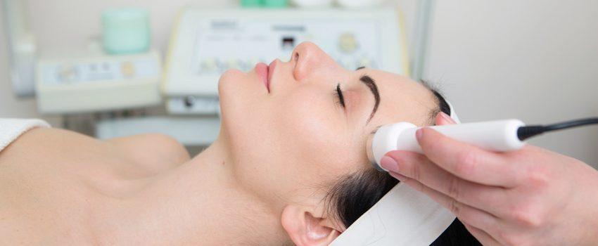 Schne junge Frau macht Ultraschall Hautreinigung und Gesichtsbeh