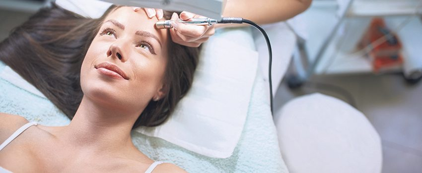 cosmetologist is undergoing microdermabrasion of skin on female