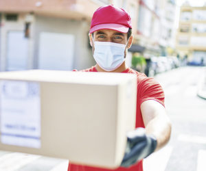 Young delivery man wearing uniform and coronavirus protection medical mask holding cardboard package at town street.