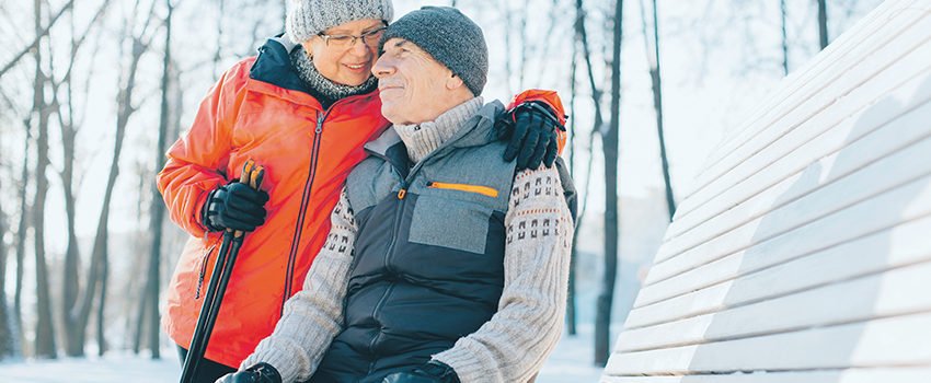 Pretty senior couple sitting with nordic walking poles in winter