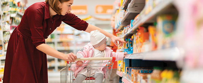 A young mother chooses baby food on a supermarket shelf and shows the products to her baby. The concept of shopping and parenting