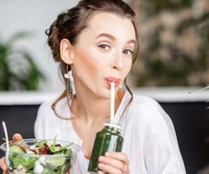 Beautiful woman with healthy food indoors