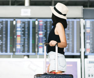 Asian adult tourist woman with travel luggage in airport termina