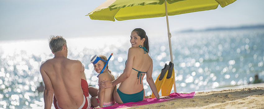 family in swimsuit  having fun at the beach  sitting under a bea